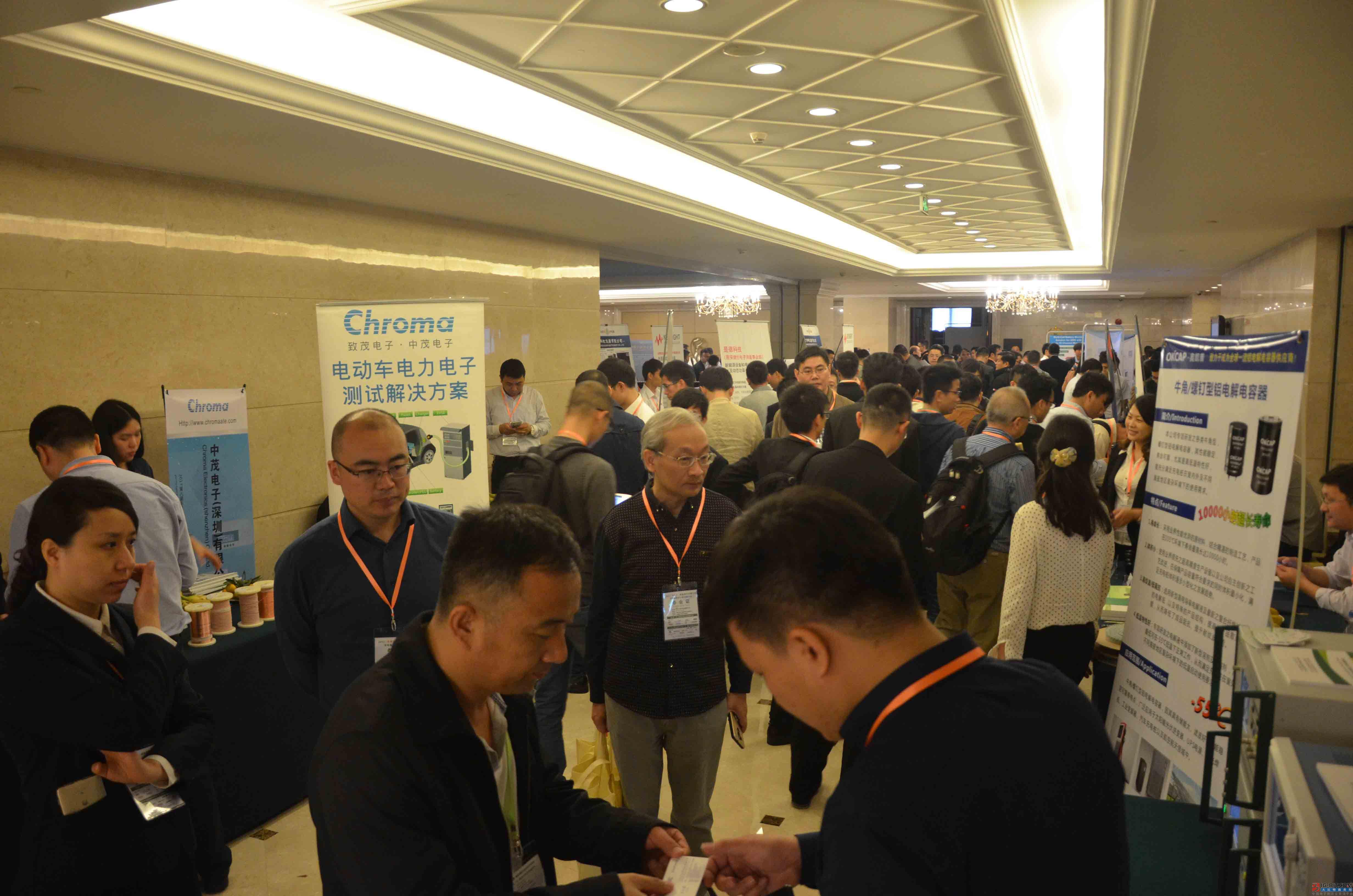 会议尚未开始,展示区已然挤满了人,与会人员在不同展位前与参展企业交流,探讨了解最新新能源充电桩技术。