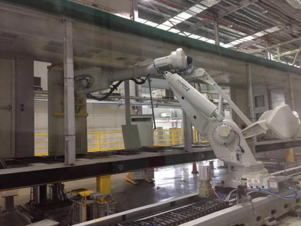 许继集团预制舱智能制造生产线上机械手臂正在抓取屏柜安装作业